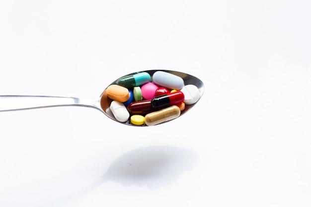 Verschiedene arten von tabletten, kapseln und pillen auf löffel