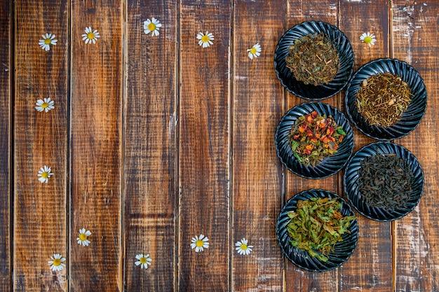 Verschiedene arten von tee auf tellern auf hölzernem hintergrund mit blumen der kamille. auswahl an trockenem tee. tee-konzept. teeblätter. draufsicht. kopieren sie platz, rahmen.