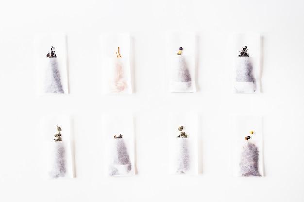 Verschiedene arten von tee in einwegfilterpackungen auf einem weißen hintergrund. draufsicht flach liegend