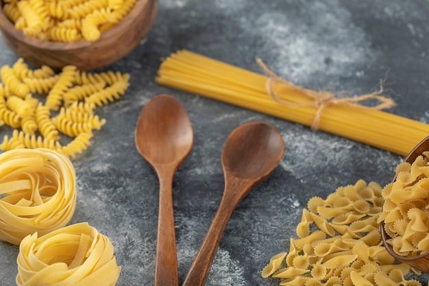 Verschiedene arten von ungekochten nudeln mit holzlöffeln.