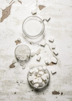 Verschiedene arten von weißzucker auf rustikalem tisch.