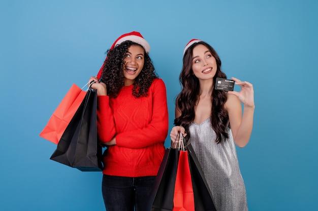 Verschiedene aufgeregte frauen mit bunten einkaufstaschen und kreditkarte