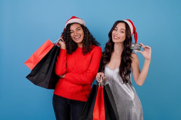Verschiedene aufgeregte frauen mit den bunten einkaufenbeuteln und kreditkarte getrennt über blau