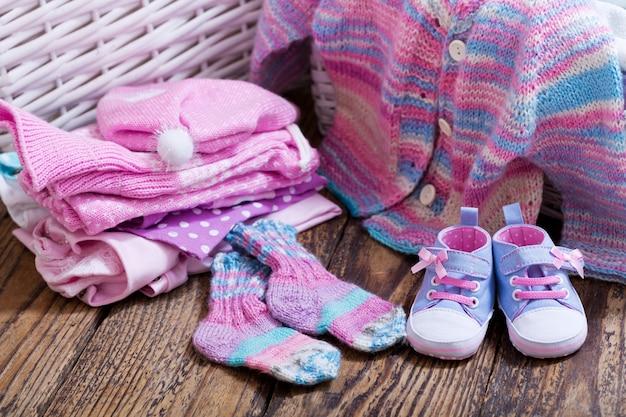 Verschiedene babykleidung auf holztisch