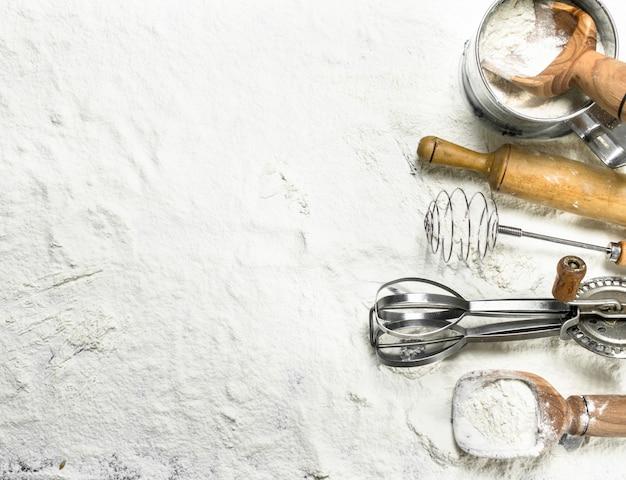 Verschiedene backwerkzeuge auf mehl. draufsicht