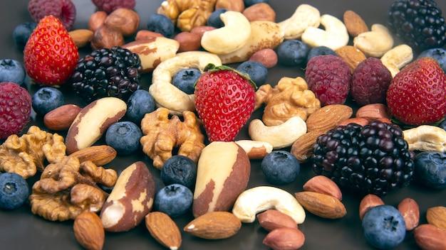 Verschiedene beeren und nüsse auf einem teller. vitaminproteine und gesunde lebensmittel
