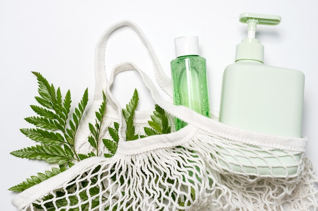 Verschiedene behälter für shampoo, conditioner oder flüssigseife im öko-beutel mit grünen blättern. null abfall, umweltfreundliches kosmetikkonzept.