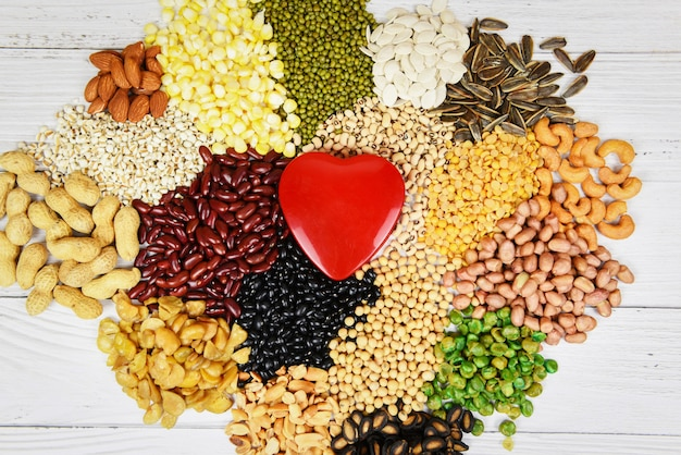Verschiedene bohnen der collage mischen die erbsenlandwirtschaft des natürlichen gesunden lebensmittels für das kochen von bestandteilen - satz verschiedene vollkornbohnen und hülsenfruchtsamenlinsen und nüsse buntes und rotes herz
