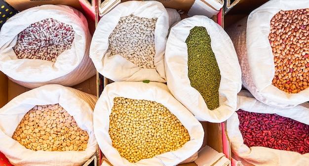 Verschiedene bohnensorten in verschiedenen farben und lupinen in säcken zum verkauf in loser schüttung auf einem lokalen flohmarkt, der in nahe gelegenen obstgärten angebaut wird