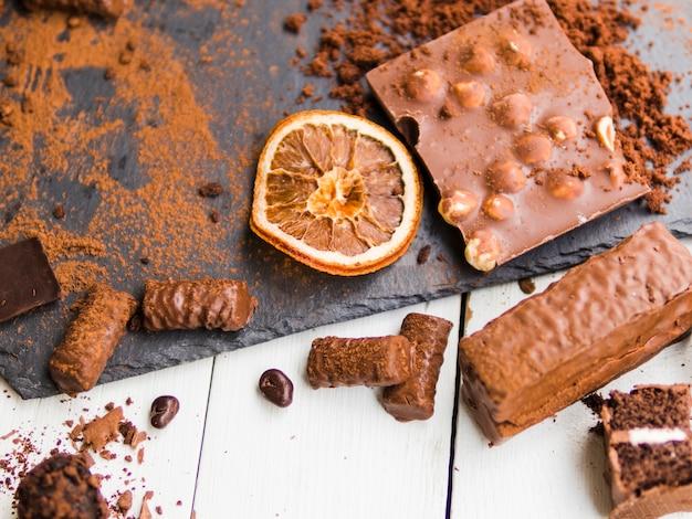 Verschiedene bonbons und pralinen mit kakaopulver