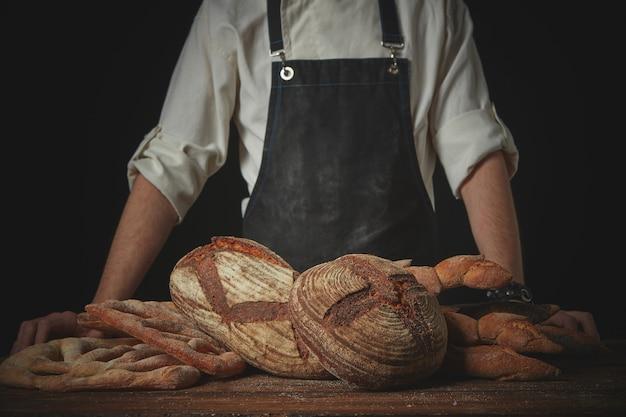 Verschiedene brotsorten auf einem braunen holztisch mit bäcker in schürze