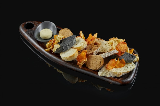 Verschiedene brotsorten - weiß-, roggen- und tinten-tintenfische auf einem holztablett auf schwarzer oberfläche. brotteller in einem restaurant