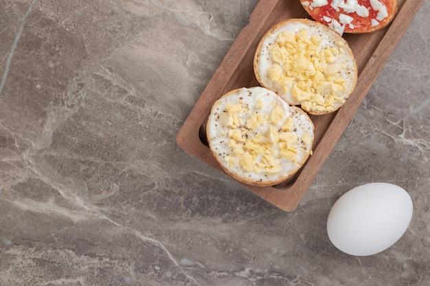 Verschiedene bruschetta auf holzteller mit eiern. hochwertiges foto