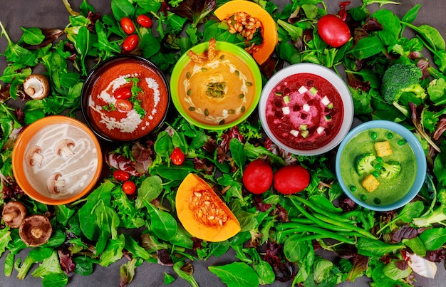 Verschiedene bunte gemüsesahnesuppen in schüsseln, essen oder vegetarisches essen.