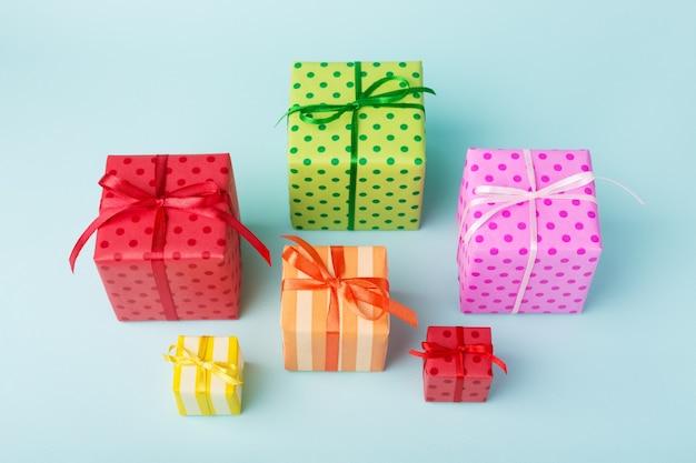 Verschiedene bunte geschenkboxen des feiertags auf blau