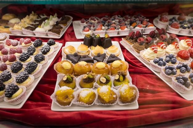 Verschiedene bunte geschmackvolle schöne kuchen auf einem showfenster im café