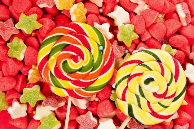 Verschiedene bunte gummibärchen und lutscher auf rotem hintergrund. draufsicht. gelee-süßigkeiten.