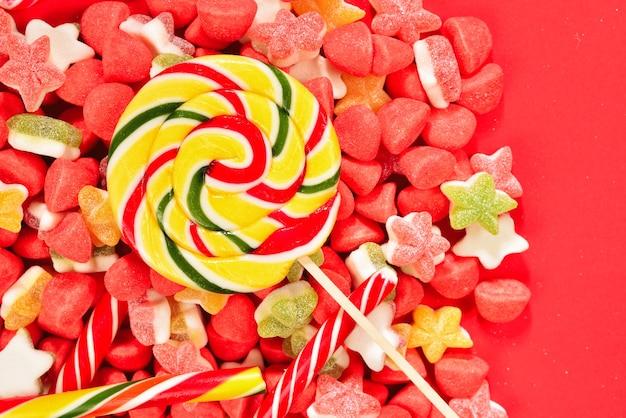 Verschiedene bunte gummibärchen und lutscher auf roter oberfläche. draufsicht. gelee-süßigkeiten.