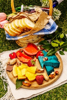 Verschiedene bunte käse und korb mit brot und wein und erdbeersaft auf kunstrasen