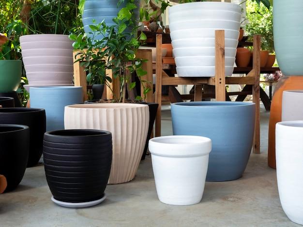 Verschiedene bunte keramikpflanzentöpfe auf betonboden angeordnet. leerer geometrischer keramikpflanzer.