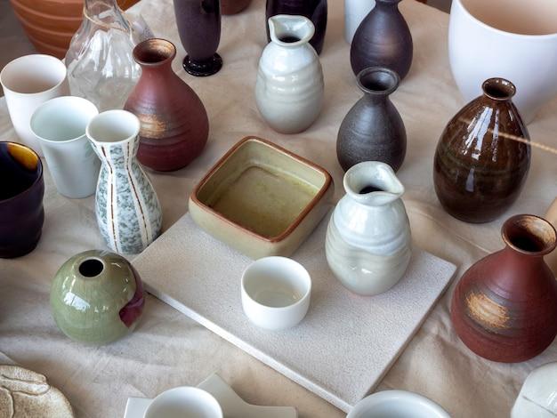 Verschiedene bunte keramikvase arrangiert auf weißem kalikogewebe, ansicht von oben. leere keramikvase.