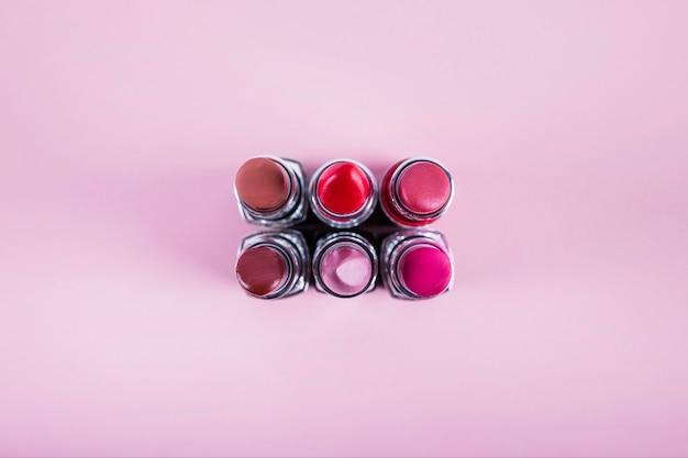 Verschiedene bunte lippenstifte auf rosa hintergrund