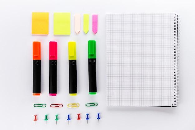 Verschiedene bunte marker mit bürozubehör auf weißem bürotisch. draufsicht. arbeitsstudienkonzept flat lay.