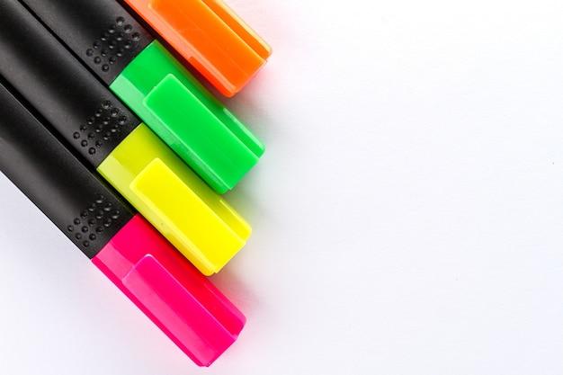 Verschiedene bunte marker mit bürozubehör auf weißem bürotisch. draufsicht. arbeitsstudienkonzept