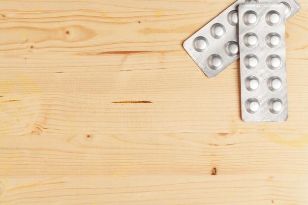 Verschiedene bunte pillen in den plastiksätzen, blasen gestapelt auf hölzernem hintergrund
