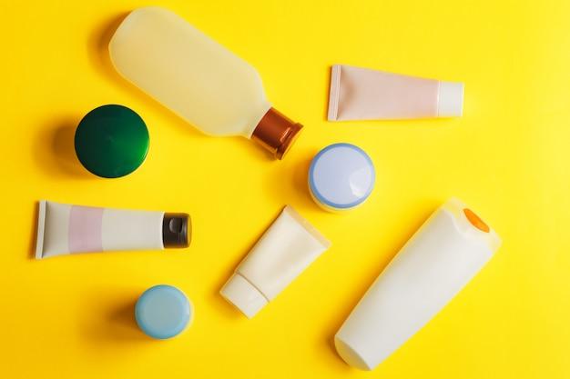 Verschiedene bunte schönheits-toilettenartikel auf gelbem hintergrund. männer und frauen pflegen produkte für haar und körper.