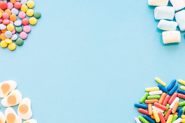 Verschiedene bunte süßigkeiten auf den blauen hintergrundecken