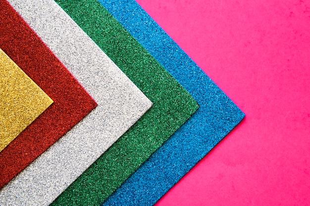Verschiedene bunte teppiche auf rosa hintergrund