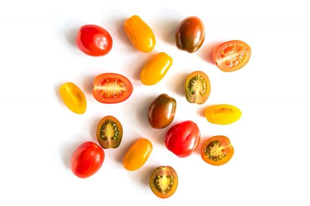 Verschiedene bunte tomaten lokalisiert auf weißer wand. draufsicht, flach liegen. kreatives layout