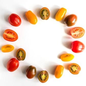 Verschiedene bunte tomaten lokalisiert auf weißer wand. gemüserahmen mit kopierraum. draufsicht, flach liegen. kreatives layout.