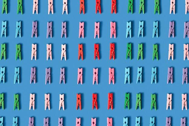 Verschiedene bunte wäscheklammern horizontales muster auf einem blau mit weichen schatten. draufsicht.