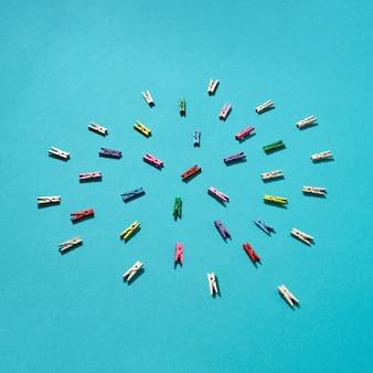 Verschiedene bunte wäscheklammern rundes muster auf einem blau mit harten schatten, kopierraum. flach liegen.