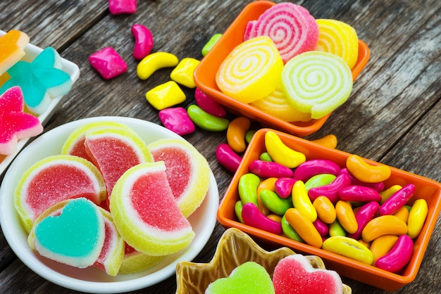 Verschiedene bunte zuckerhaltige süßigkeit im behälter auf alter hölzerner planke