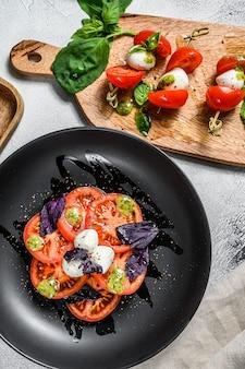 Verschiedene caprese-salate, spieße, häppchen, bruschettes mit kirschtomaten, mozzarella und basilikum. grauer hintergrund. draufsicht