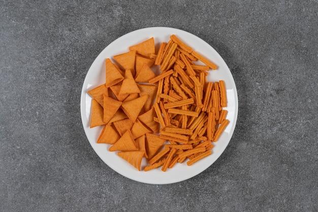 Verschiedene chips auf der platte auf der marmoroberfläche