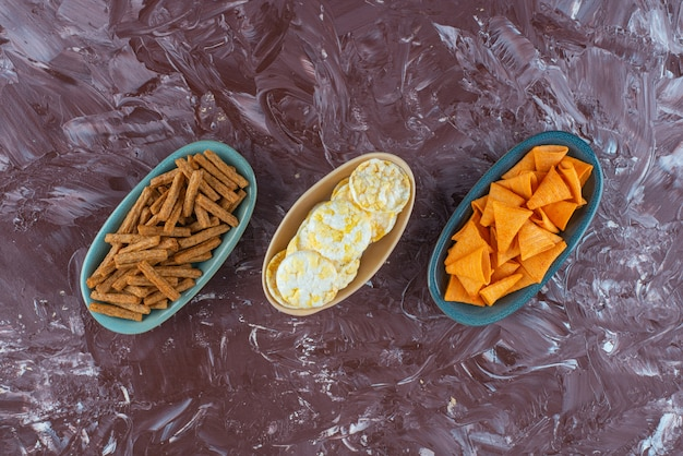 Verschiedene chips in schalen, auf dem marmortisch.