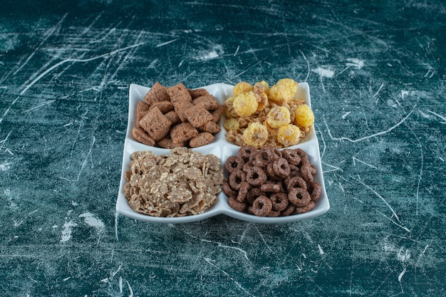 Verschiedene cornflakes in einer schüssel auf blauem hintergrund. foto in hoher qualität