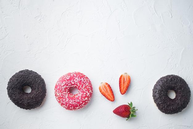 Verschiedene dekorierte donuts auf weißem tisch, draufsicht flach gelegt