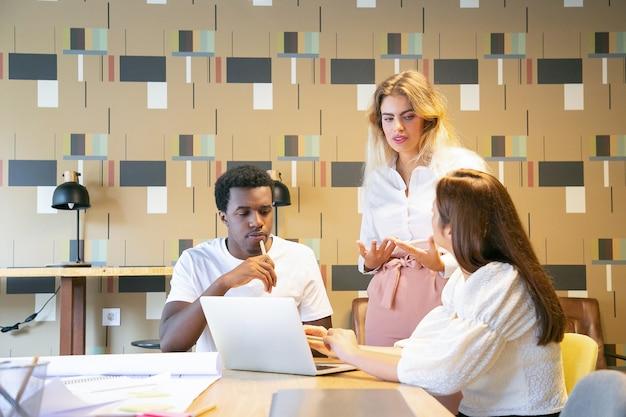 Verschiedene designer diskutieren das projekt mit dem teamleiter