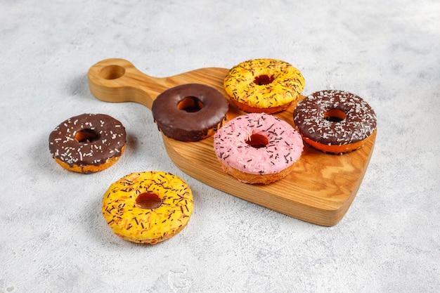 Verschiedene desserts mit schokoladenglasur, rosa glasur und streuseln.