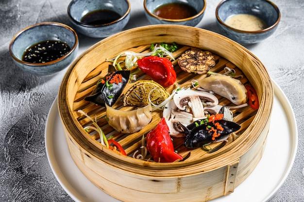 Verschiedene dim-sum-vorspeisen in einem bambusdampfer. satz chinesisches essen. grauer hintergrund. draufsicht