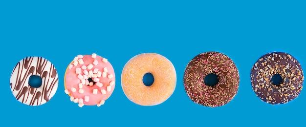 Verschiedene donuts mit schokolade gefrostet, rosa glasiert und streusel auf blauem großen hintergrund mit kopierraum. auswahl an verschiedenen bunten donuts.