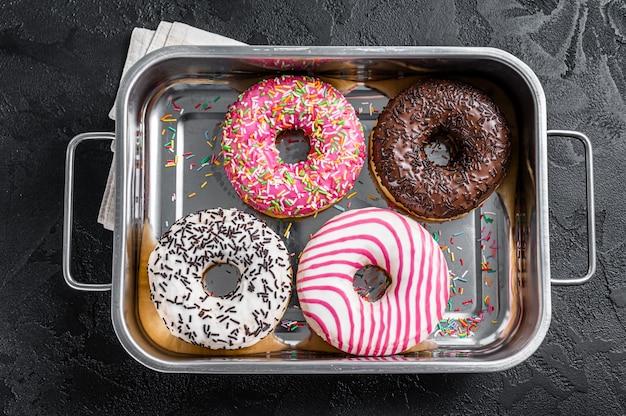 Verschiedene donuts mit schokolade, rosa glasiert und streuseln donut. schwarzer hintergrund. ansicht von oben.