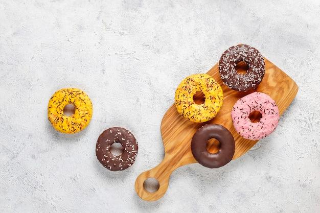 Verschiedene donuts mit schokoladenglasur, rosa glasiert und streuseln.