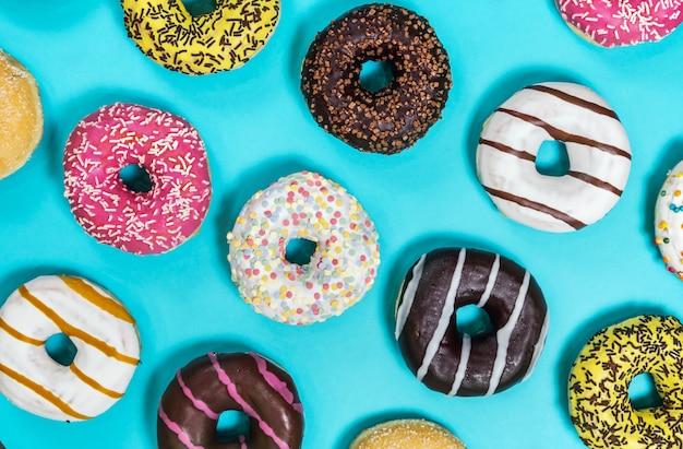 Verschiedene donuts mit verschiedenen füllungen und zuckerguss auf einem blauen rücken