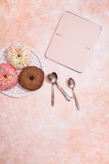 Verschiedene doughnuts mit schokolade mattiert; rosa glasiert und besprüht schaumgummiringe auf weißem plattenlöffel und leerem notizbuch gegen rustikalen hintergrund